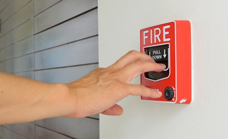 hand pulling the fire alarm at a business