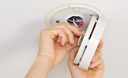 hands installing a fire alarm and smoke detector on the ceiling